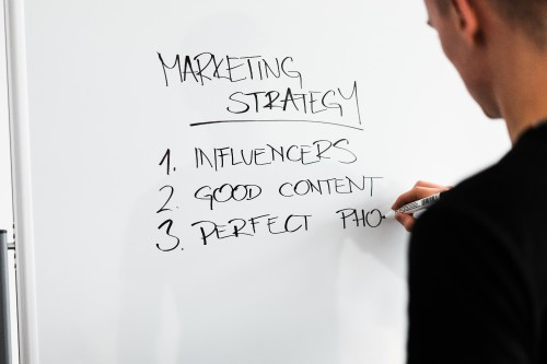 marketing-expert-writing-new-marketing-strategy-on-whiteboard.jpg